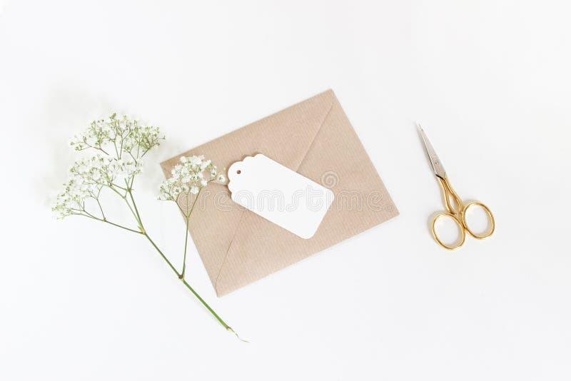 Den vita gåvaetiketten med hantverkpapperskuvertet, den guld- saxen och behandla som ett barn för andedräktgypsophilaen för ` som royaltyfri bild