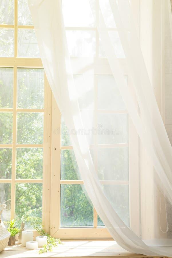 Den vita höjdpunkten för gardin- och träfönsterramen stämmer bakgrund med solljus arkivfoton