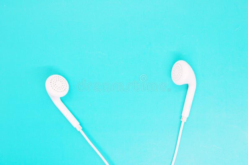 Den vita hörlurar stänger sig upp på en turkosbakgrund, hörlurar för att lyssna till musik, moderna grejer, ungdomtillbehör royaltyfri foto