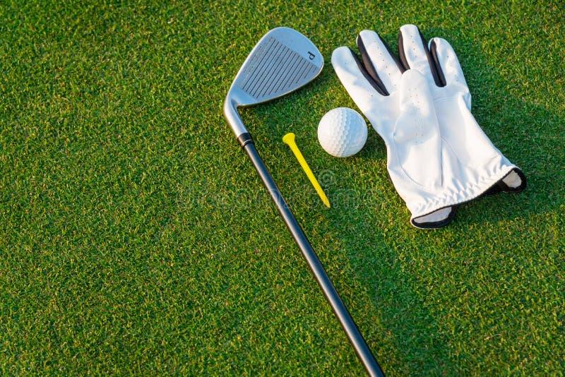 Den vita handsken för golfsportutrustning, golfbollen, golfklubben och den gula utslagsplatsgolfen med grönt gräs royaltyfri foto