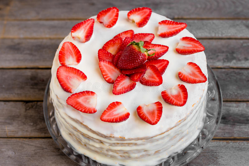 Den vita kakan dekorerade med jordgubbar som förlades på en trätabell fotografering för bildbyråer