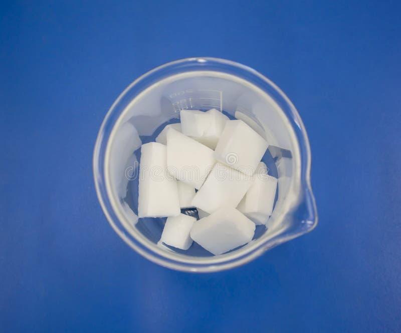 Den vita kemiska ingrediensen i klar dryckeskärl på blått bordlägger backgrou arkivfoto