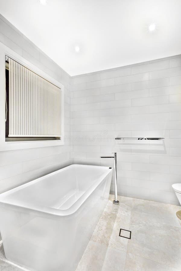 Den vita keramiska badningen badar i lyxigt rum royaltyfri fotografi