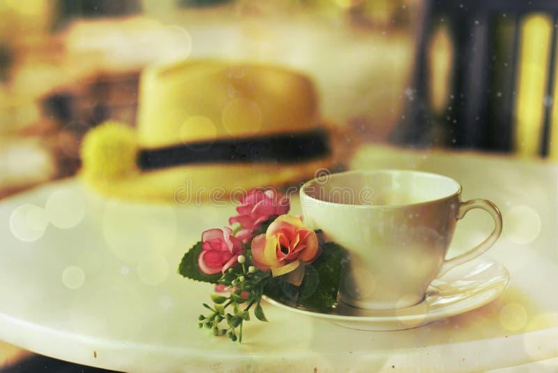 Den vita koppen av varmt te och Straw Hat med tappning utformar royaltyfri bild