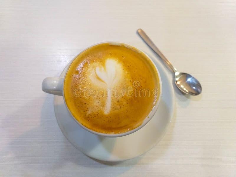 den vita koppen kaffe med mjölkar en metallisk tesked på ett vitt tefat på en vit tabell arkivfoton