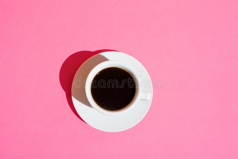 Den vita koppen kaffe med rosa färger för tefatonNeonfuchsia färgar bakgrund Mode för böjelse för koffein för morgonfrukostenergi arkivbild