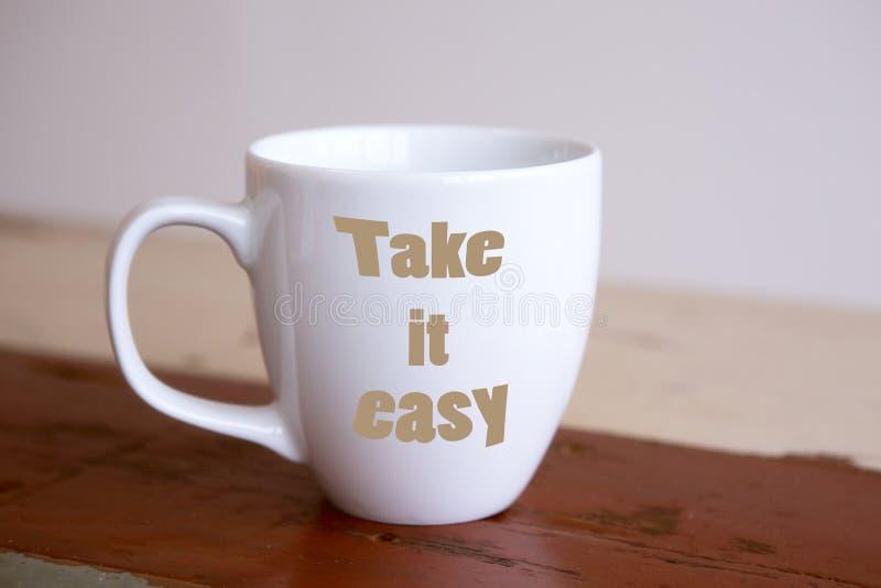 Den vita koppen med orden tar det som är lätt royaltyfria bilder