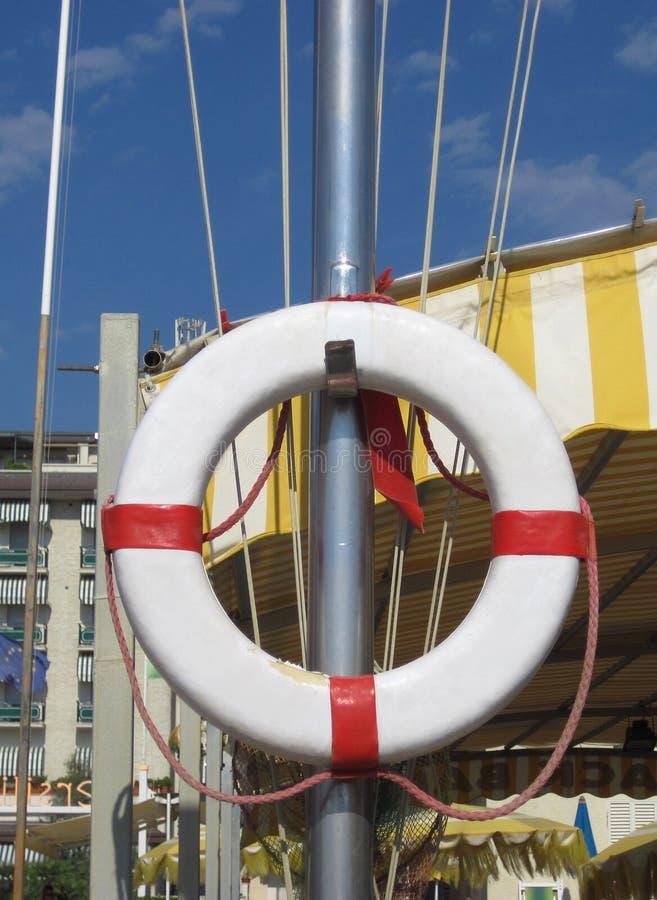 Den vita livbojet med rep hänger på en mast royaltyfri foto