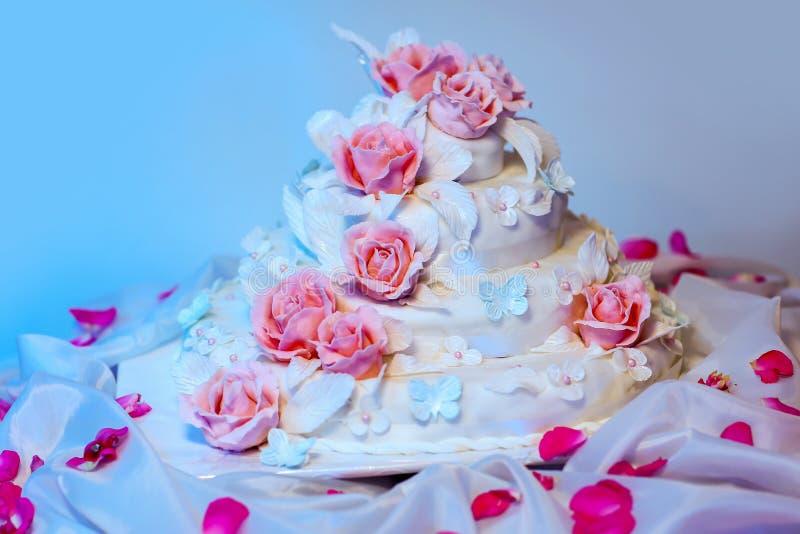 Den vita mång- jämna bröllopstårtan med rosa rosor blommar garneringar arkivfoton