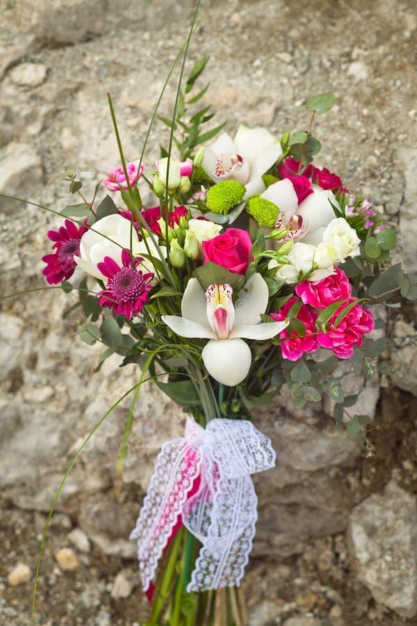 Den vita och rosa gifta sig buketten på vaggar bakgrund arkivfoto
