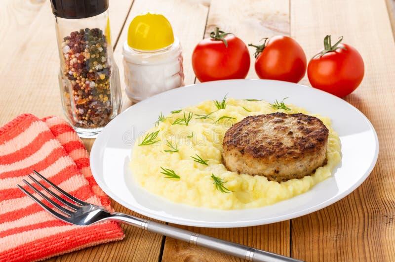Den vita plattan med kotletten, mosad potatis, saltar shaker, smaktillsatsen, tomater, gaffel på trätabellen royaltyfri foto