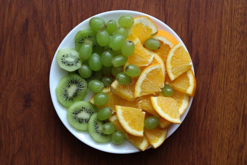 Den vita plattan som fylls med olika frukter, står på en trätabell royaltyfri fotografi