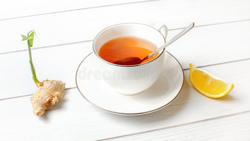 Den vita porslinkoppen med varmt bärnstensfärgat te, försilvrar skeden i den, rotar den torra ingefäran den gröna grodden och sty royaltyfria bilder
