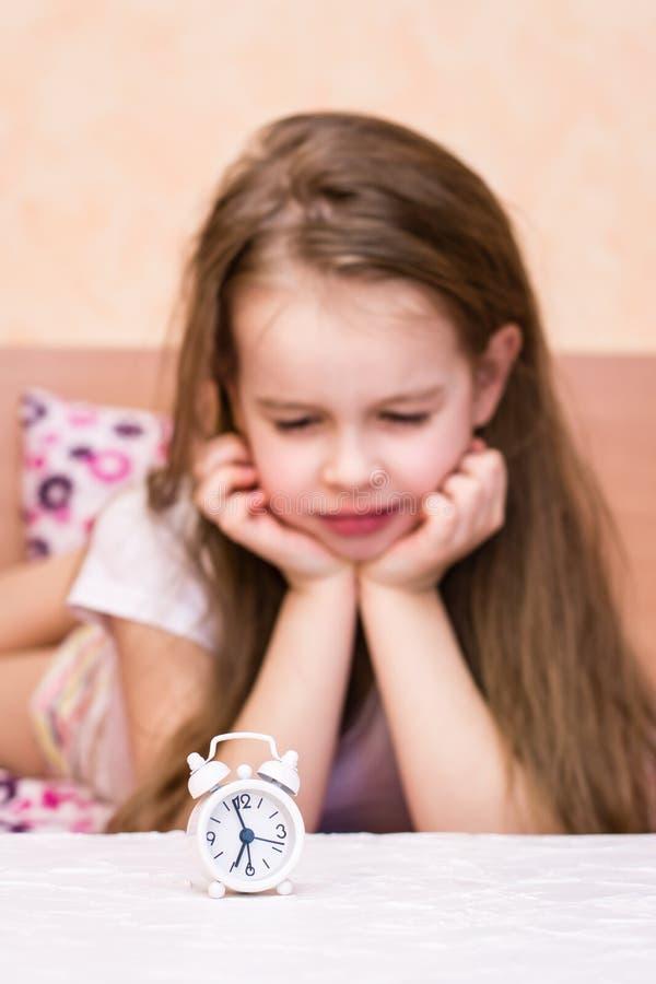 Den vita ringklockan står på tabellen på bakgrunden av en missnöjd väckt flicka arkivfoton
