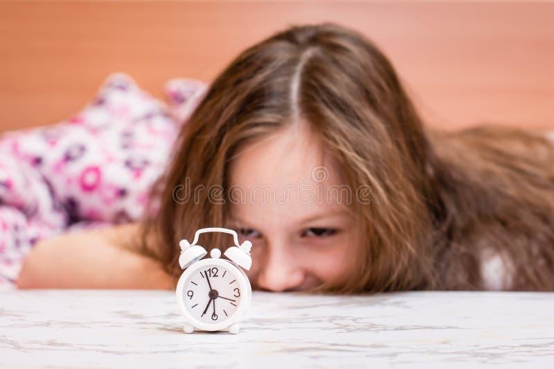Den vita ringklockan står på tabellen på bakgrunden av vakna upp flickan arkivfoto