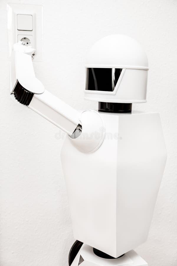 Den vita roboten laddar sig upp royaltyfri fotografi