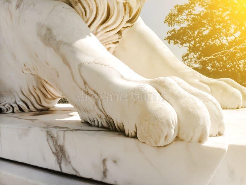 Den vita skulpturnärbilden av marmorerar kraftigt tafsar av ett lejon på en sockel i solljuset royaltyfri foto