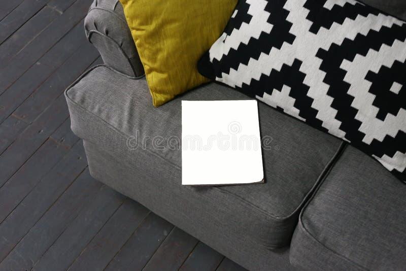 Den vita soffan för notepadaffischhandstil kudde inre royaltyfri foto