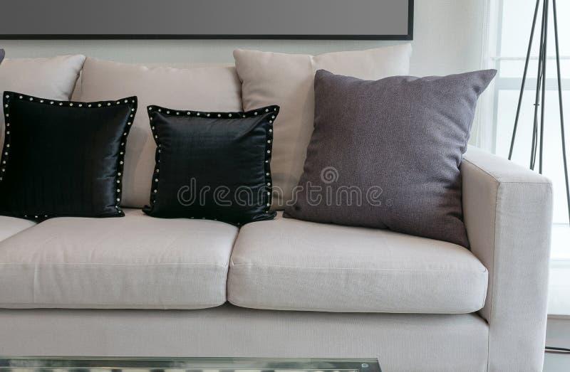 Den vita soffan med svart och grå färger kudde i vardagsrum fotografering för bildbyråer
