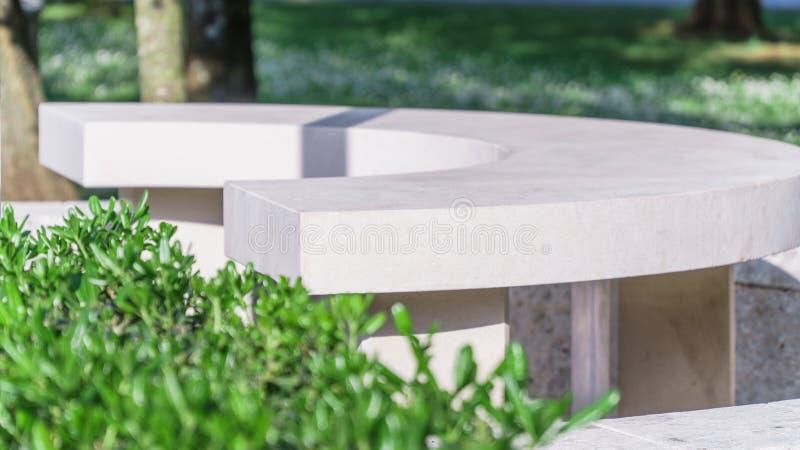 Den vita stenbänken i en sommar parkerar arkivfoto