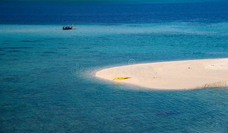 Den vita stranden med den gula kanoten i det tropiska havet arkivfoton