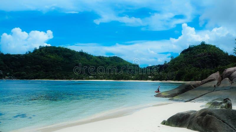 Den vita stranden på Seychellerna med vaggar och kanoten royaltyfri fotografi
