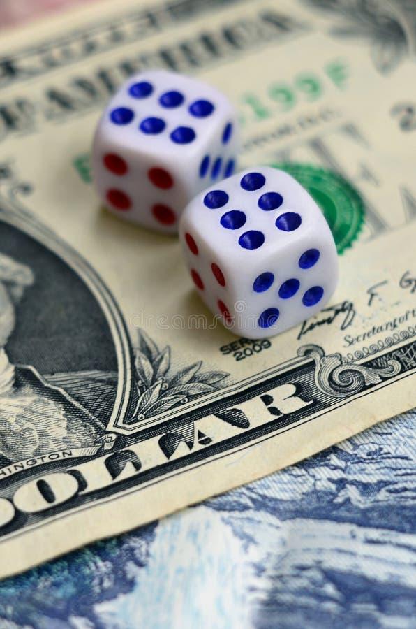 Den vita tärningen är på en dollarräkning av US dollar Begreppet av dobblerit med hastigheter i monetär enhet royaltyfri bild