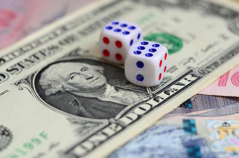 Den vita tärningen är på en dollarräkning av US dollar Begreppet av dobblerit med hastigheter i monetär enhet royaltyfri foto