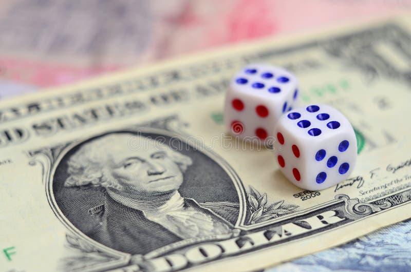 Den vita tärningen är på en dollarräkning av US dollar Begreppet av dobblerit med hastigheter i monetär enhet royaltyfria foton