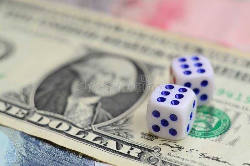 Den vita tärningen är på en dollarräkning av US dollar Begreppet av dobblerit med hastigheter i monetär enhet arkivfoto