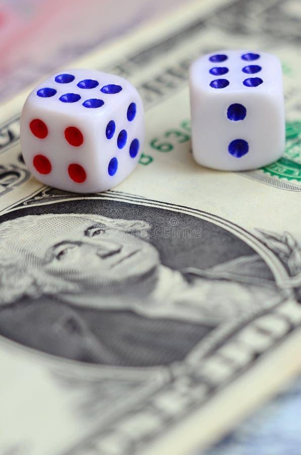 Den vita tärningen är på en dollarräkning av US dollar Begreppet av dobblerit med hastigheter i monetär enhet arkivbild