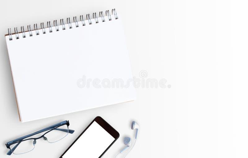 Den vita tabellen för kontorsskrivbordet med bärbar datordatoren och ilar telefonen royaltyfria foton