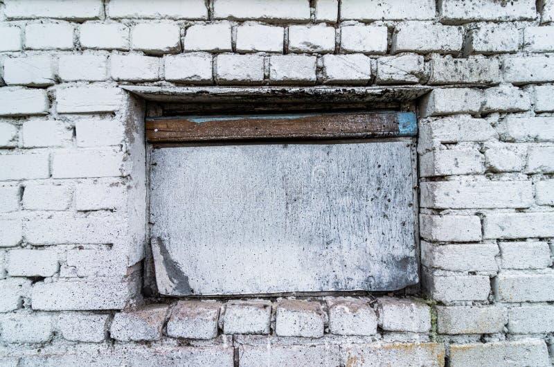 Den vita tegelstenväggen med ett fönster, byggnadsstrukturer, övergav byggnad arkivfoto