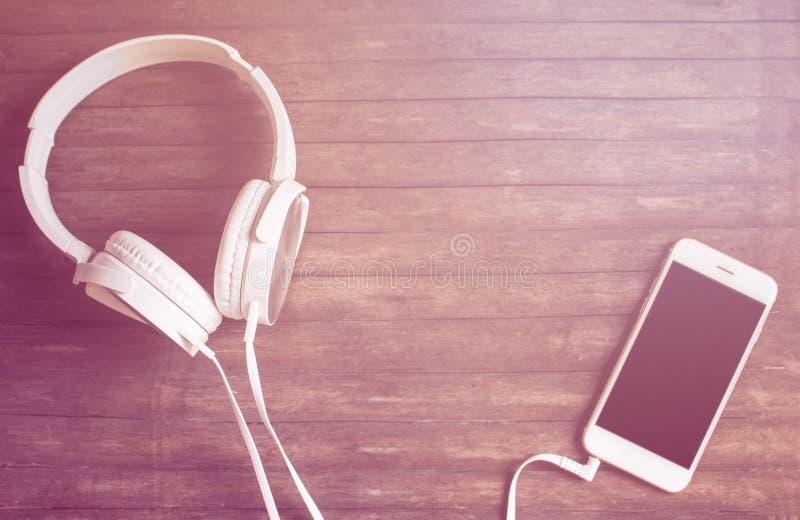 Den vita telefonen och hörlurar sänker lägger på trätabellen Varmt rosa ljus tonat foto royaltyfria bilder