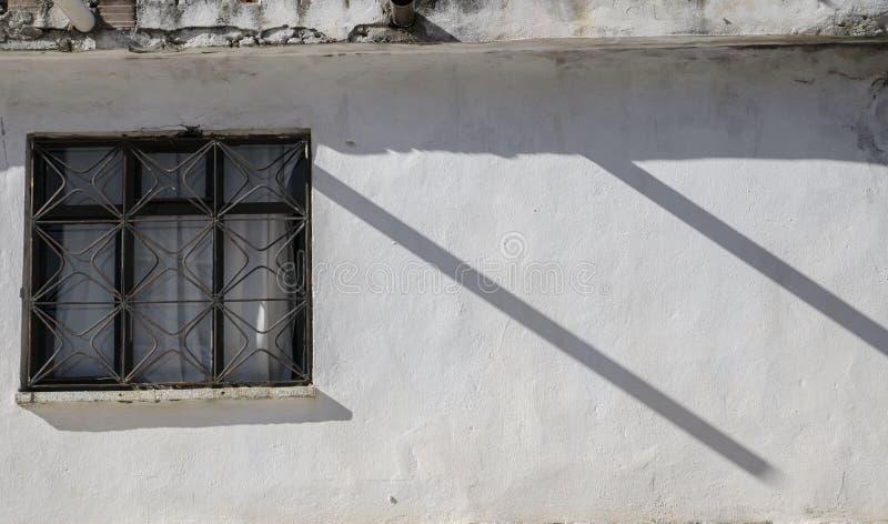 Den vita väggen av huset, ett fönster på väggen, två parallella skuggor skapar en rytm i fotoet, fotografering för bildbyråer
