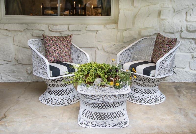 Den vita vide- stolar och tabellen utanför på all farstubron med höstblommaordning med hjorthorn mot vit målade stenväggen royaltyfria bilder