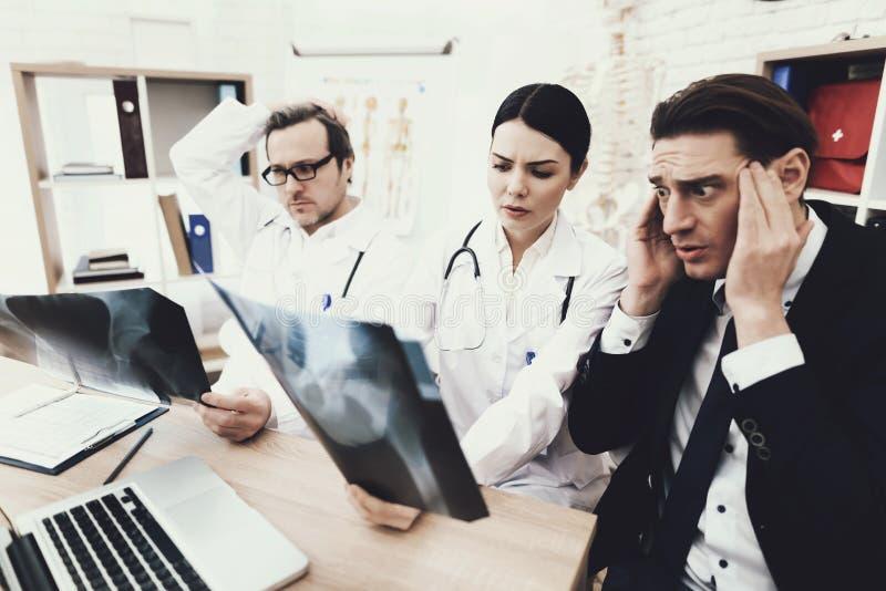 Den vuxna affärsmannen förskräckas av diagnos av doktorn som håller röntgenbild i medicinskt kontor arkivbilder