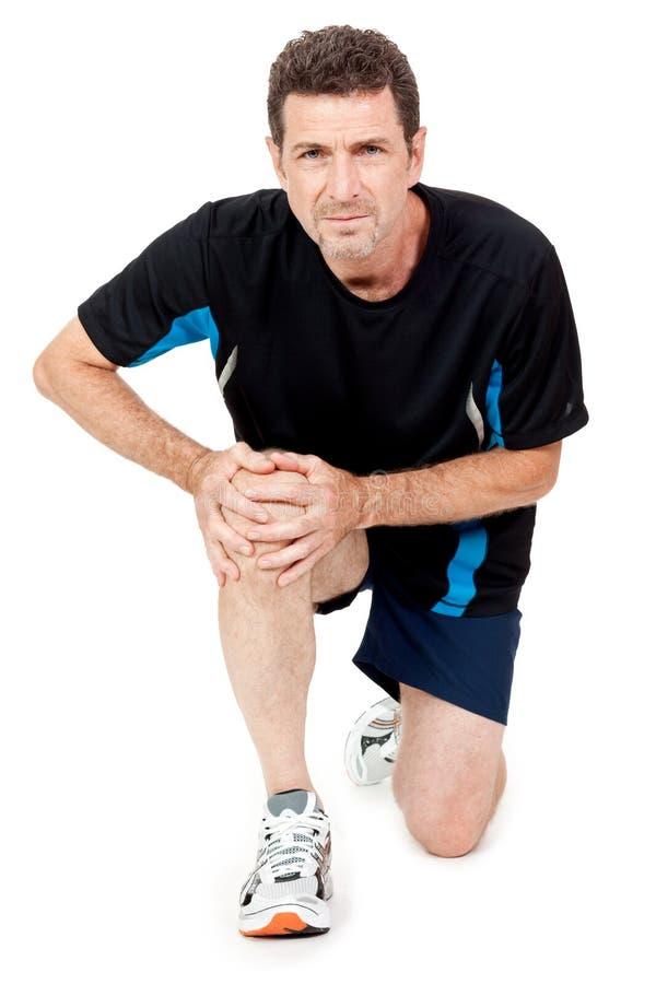 Den vuxna attraktiva mannen i det isolerade sportswearknäet smärtar skadaknip royaltyfri bild
