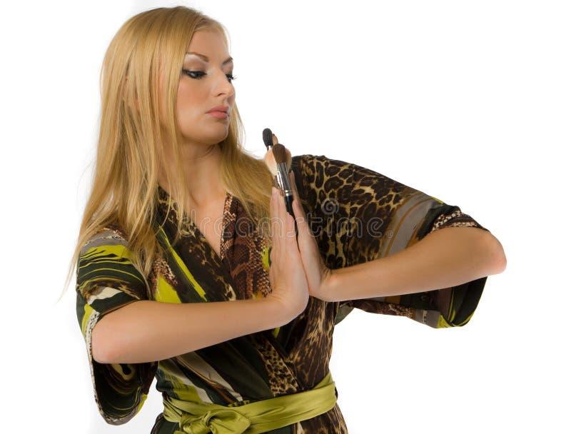 den vuxna blondinen brushes makeup royaltyfri bild