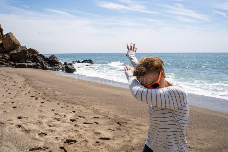 Den vuxna caucasionkvinnan gör en badda dansflyttning medan på stranden Taget på punkt Dume Malibu Kalifornien royaltyfria foton