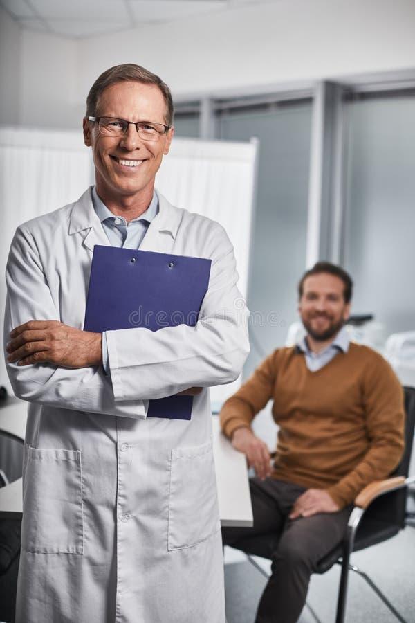Den vuxna doktorn rymmer mappar i hans händer arkivfoto