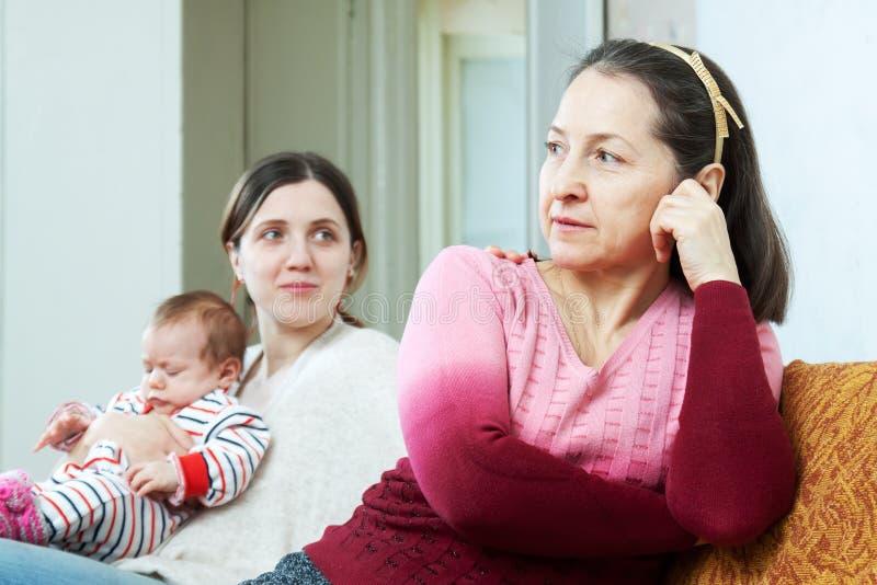 Den vuxna dottern med behandla som ett barn frågar för förlåtelse från fostrar royaltyfri bild