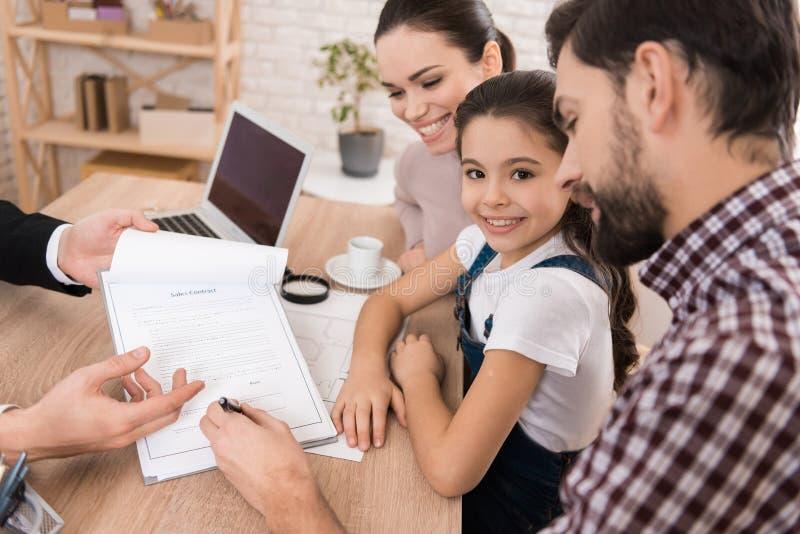 Den vuxna fadern med frun och dottern undertecknar försäljningsavtalet i regeringsställning av fastighetsmäklaren arkivfoto