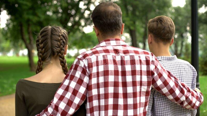 Den vuxna fadern som går med dottern, och sonen parkerar in, kramar och talar, familjen arkivfoto