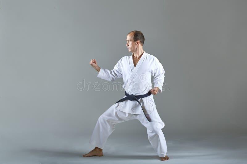 Den vuxna idrottsmannen utbildar formella karateövningar arkivbild