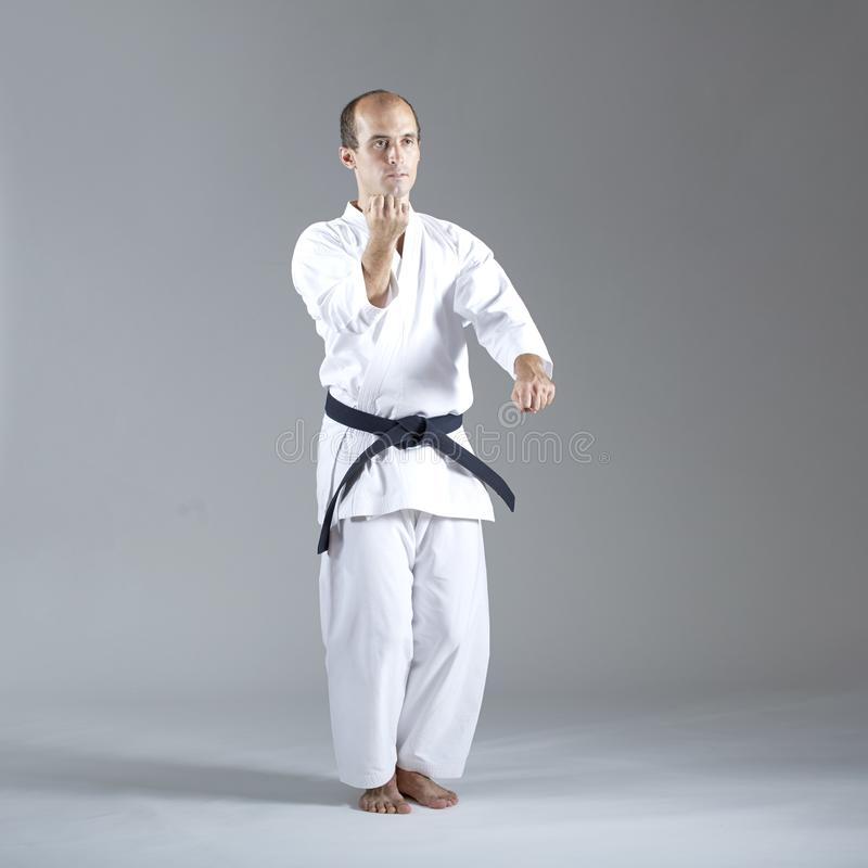 Den vuxna idrottsmannen utför formella övningar av karate royaltyfria foton