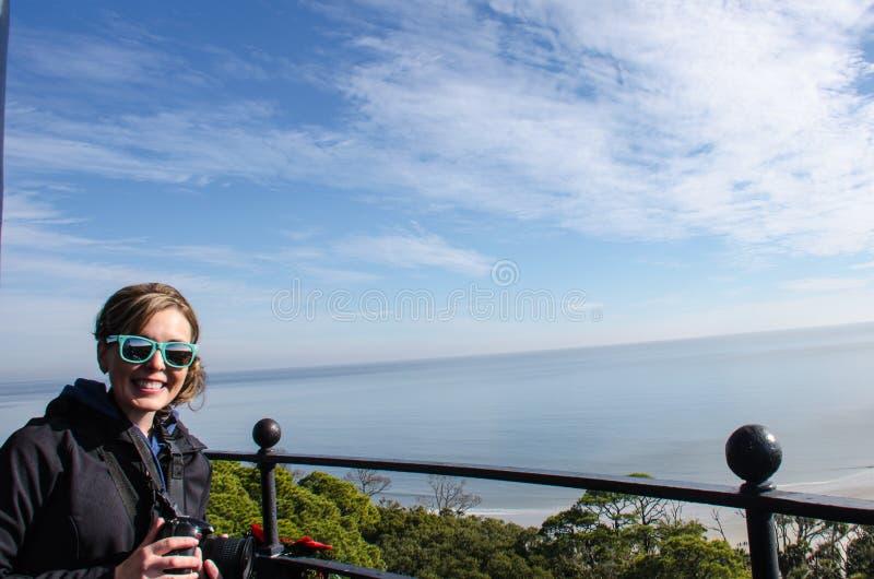 Den vuxna kvinnan ler och tycker om sikten, når han har klättrat överkanten av jaktöfyren royaltyfri bild