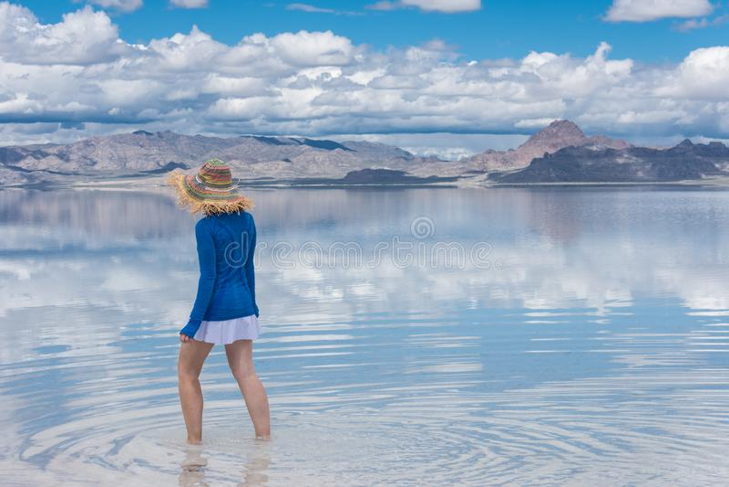 Den vuxna kvinnan som bär en hatt, går i de översvämmade Bonneville salta lägenheterna i Utah royaltyfri fotografi