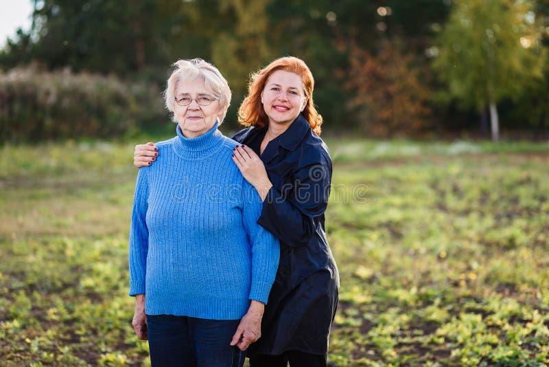 Den vuxna kvinnlign kramar en äldre moder royaltyfria foton