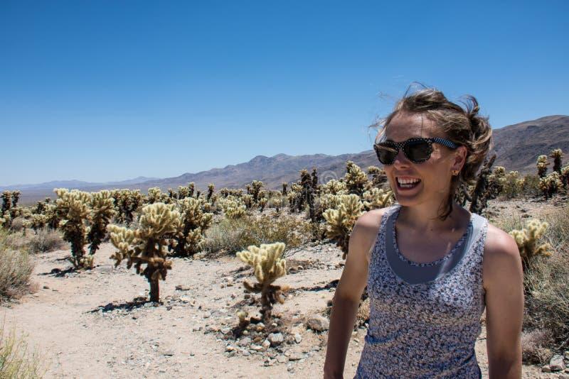 Den vuxna kvinnlign ler bland ett fält av den Cholla kaktuns i Joshua Tree National Park arkivfoton